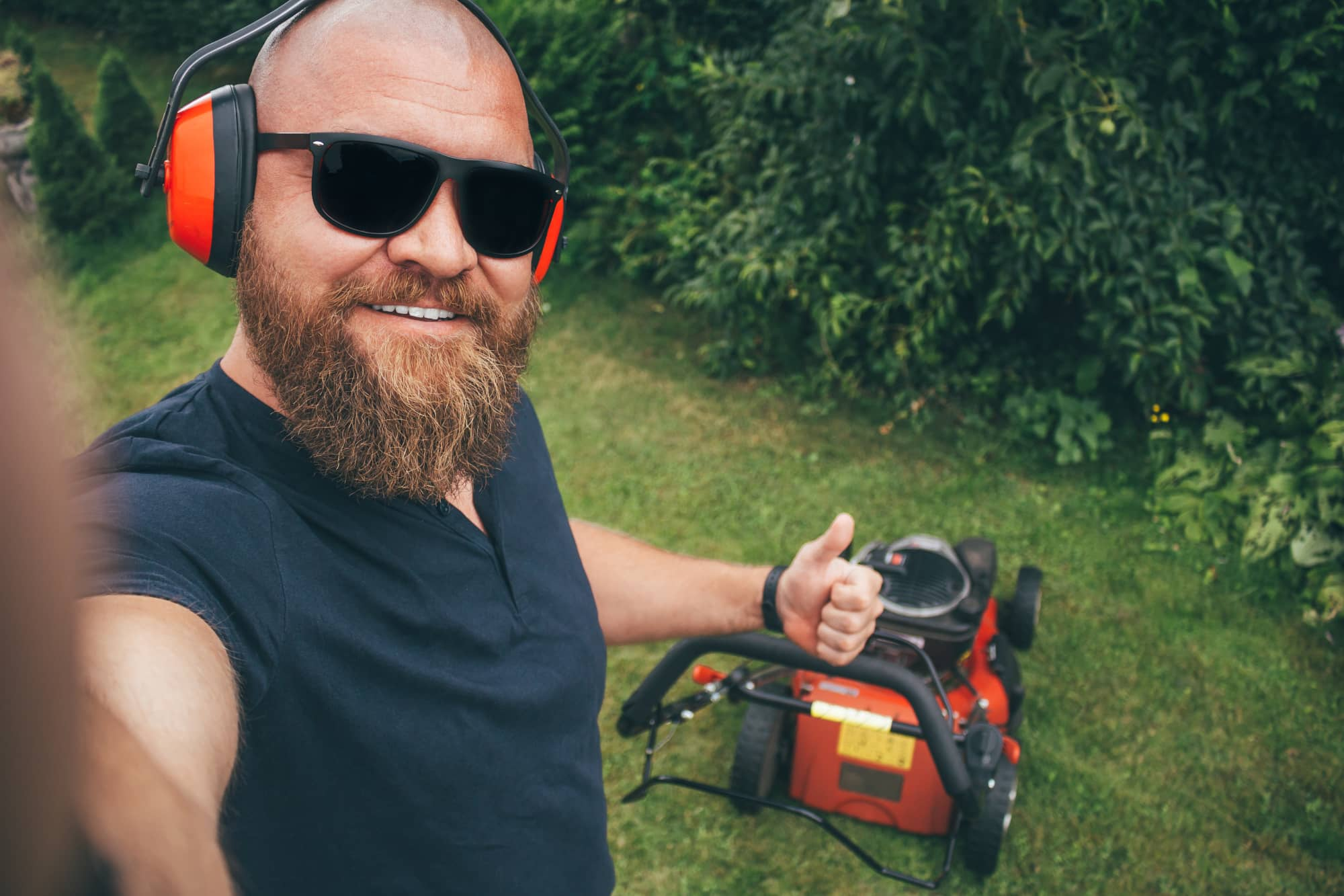 Bearded man mowing lawn