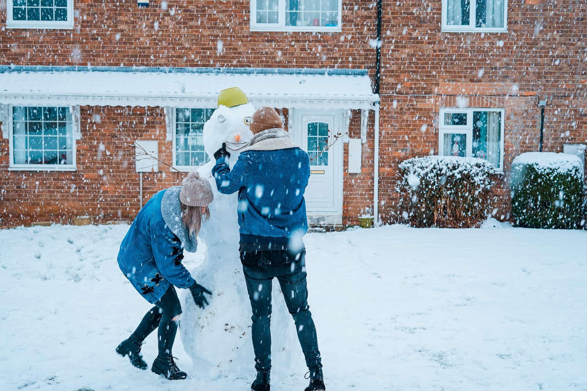Couple building snowman