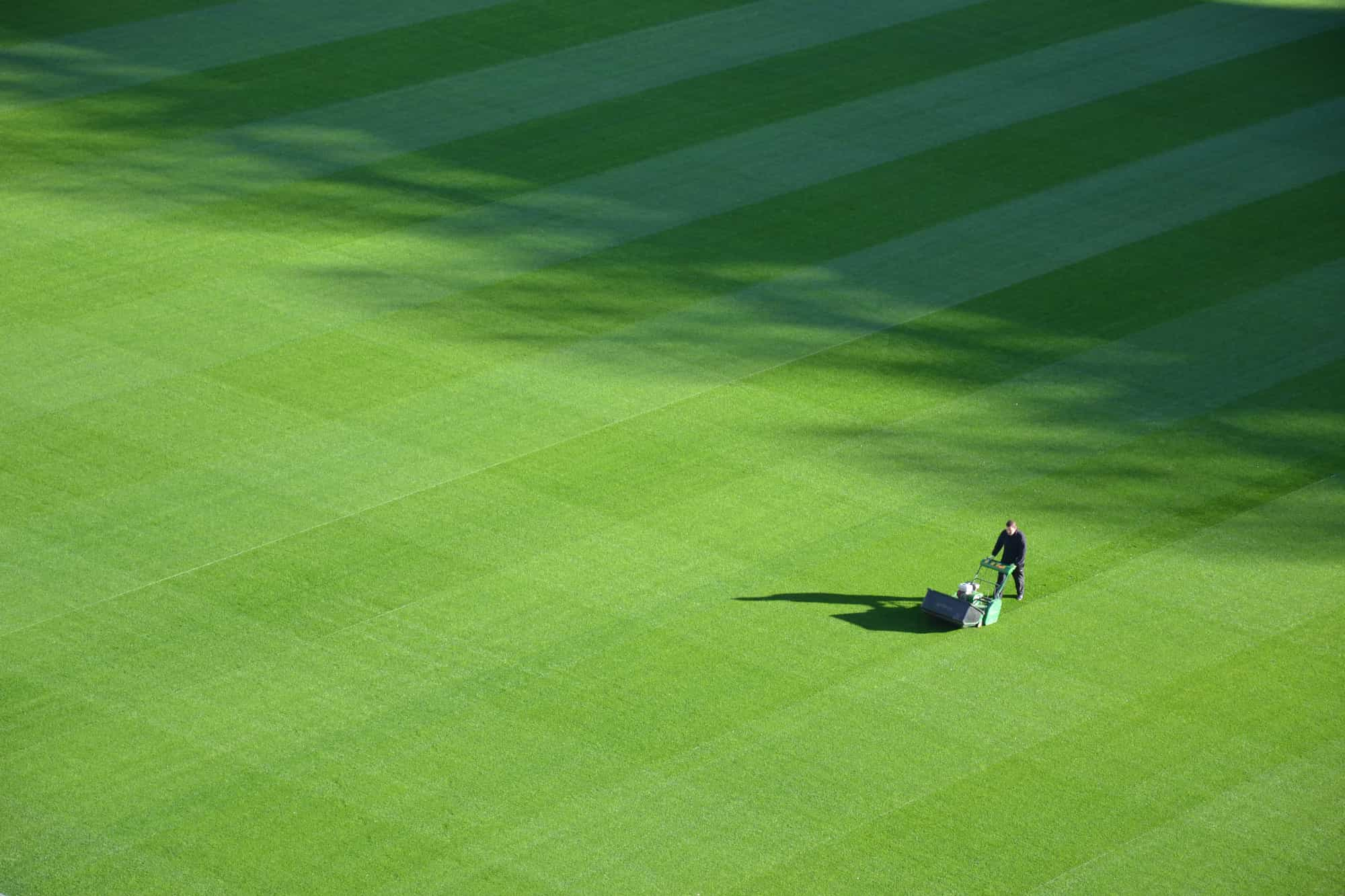 man using a lawn mower on a field
