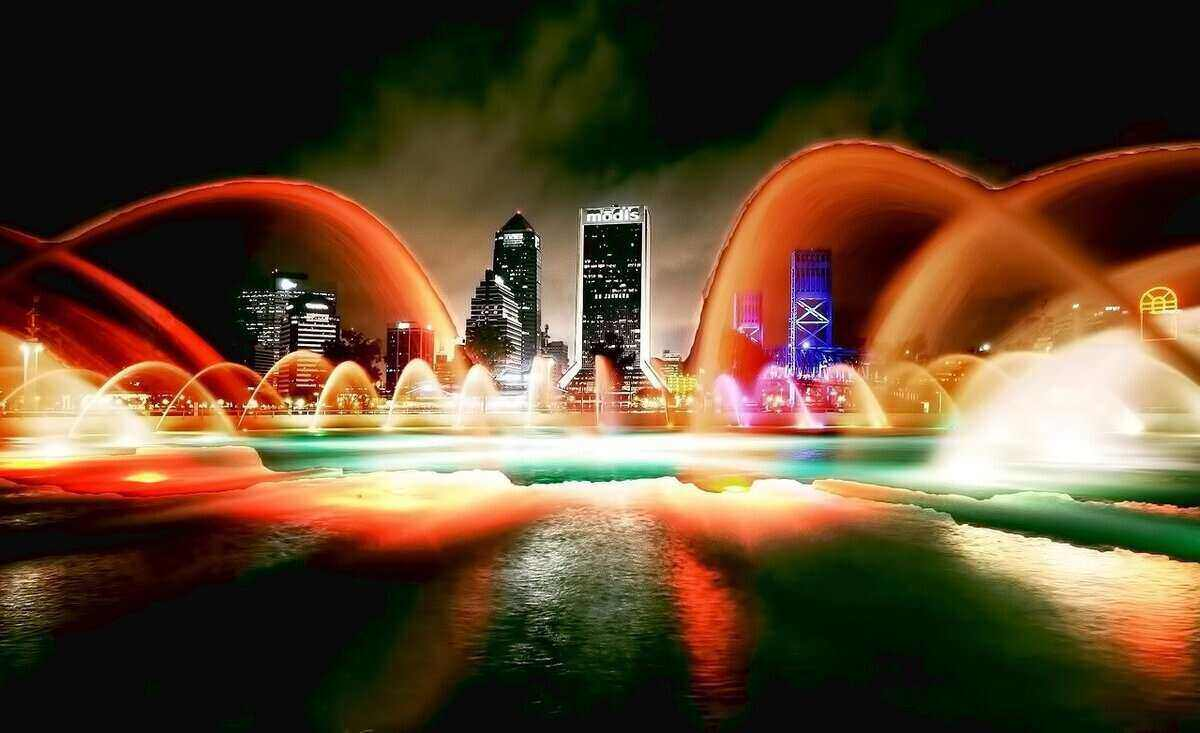 Jacksonville, Florida, skyline at night in background with colorful fountain in the foreground.