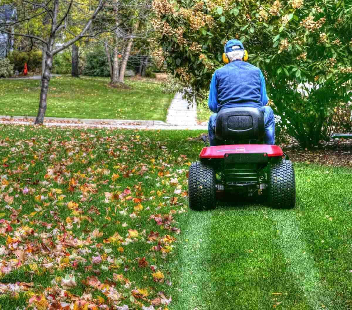 Senior man mowing lawn and mulching leaves using a riding lawn mower