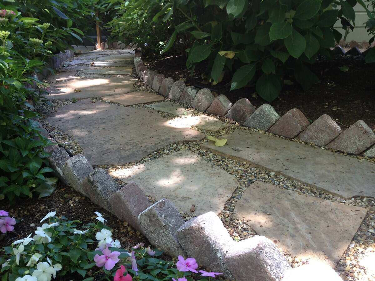 A path cut through a garden that is made of brick and stone with landscaping along either side