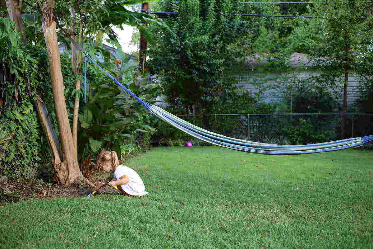 Young girl holding gardening tools and digging around a tree in the yard with a hammock in the background