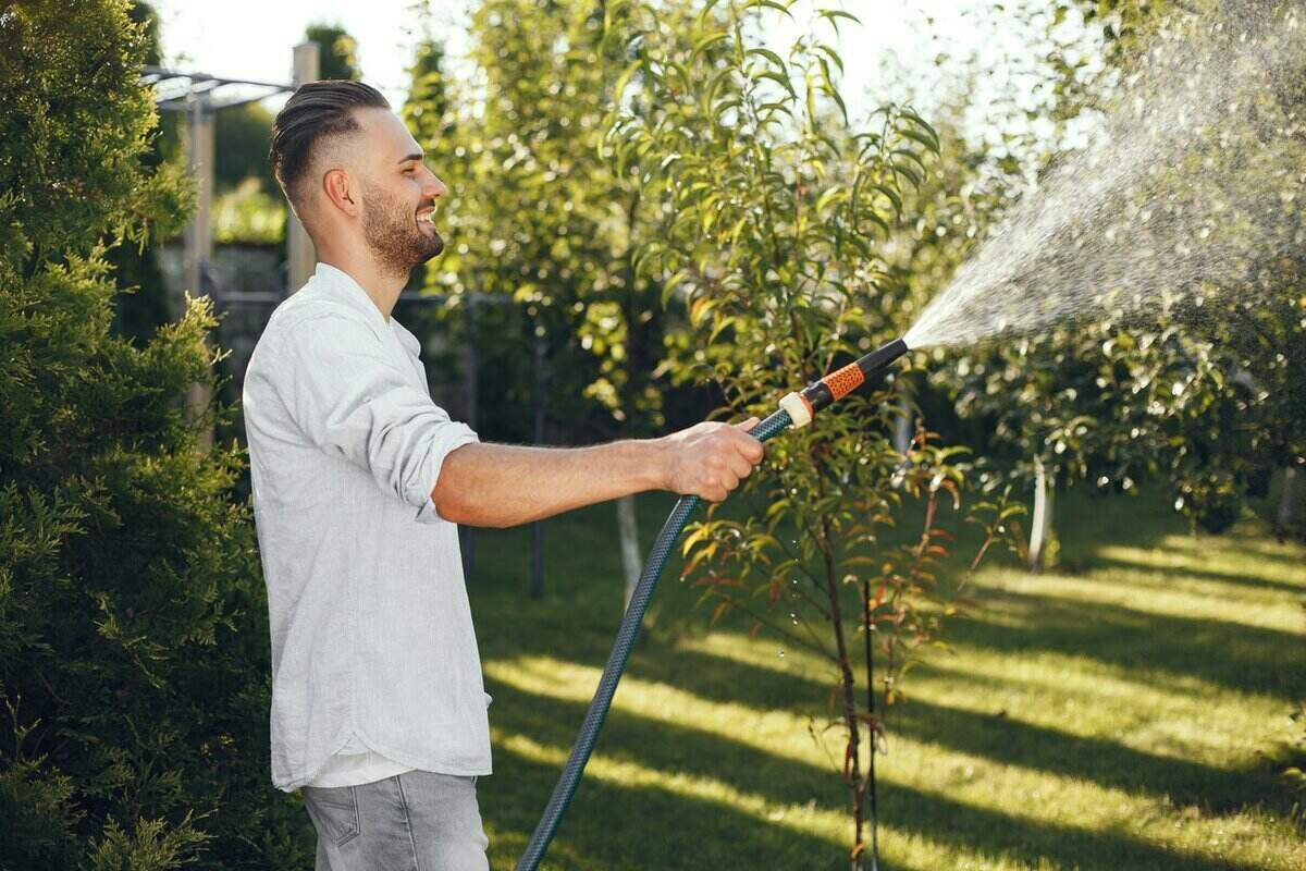 Man smiling while watering his lawn with a hose