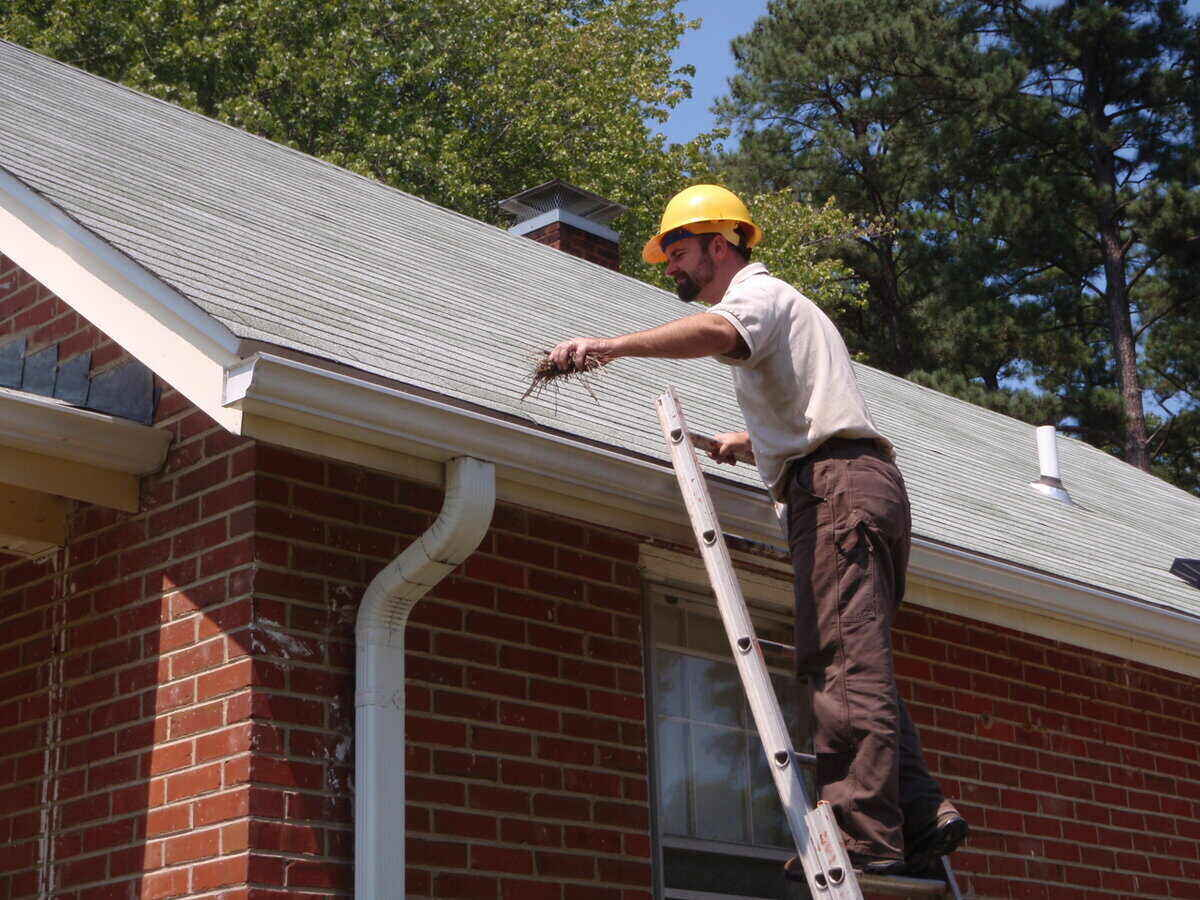 Man wearing a hard hat and on a ladder removing debris from a roof gutter